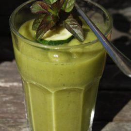 Ein großes Glas mit einem grünen Smoothie, garniert mit einer rohen Zucchinischeibe und Pfefferminzblättern
