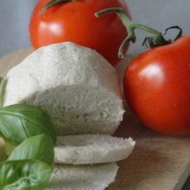 Ein Holzbrett mit zur Hälfte geschnittenem Mozzarella, Basilikumblättern und prallen Tomaten