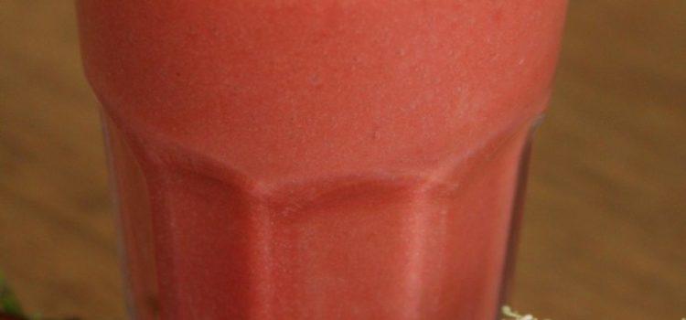 Ein Glas mit einem rosa Smoothie, dekoriert mit Erdbeeren und Holunderblüten