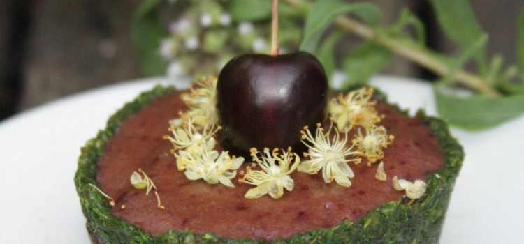Ein Törtchen garniert mit einer Kirsche und Lindenblüten
