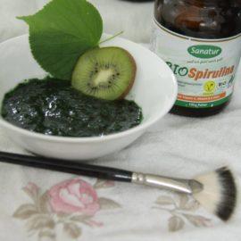 Eine kleine weiße Schüssel mit einer grünen Gesichtsmaske, einer Scheibe Kiwi und einem Lindenblatt. Daneben ein Glas mit Spirulina und ein Maskenpinsel