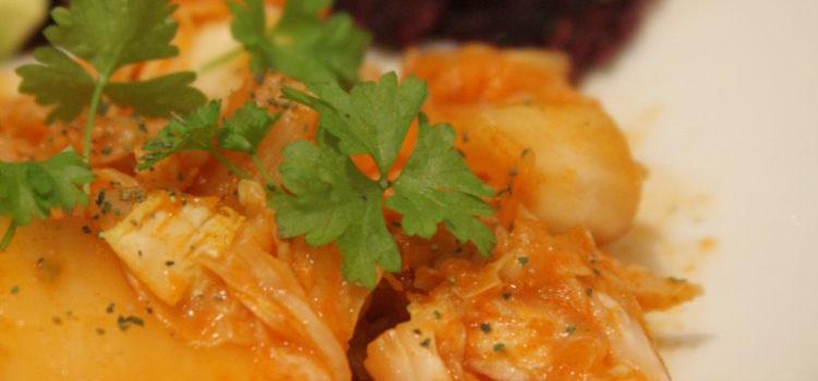 Kimchi auf einem Teller mit Rohkostkräckern und Avocado