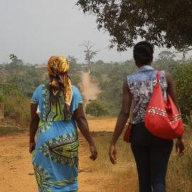 Zwei afrikanische Frauen gehen auf einer Straße, fotografiert von hinten