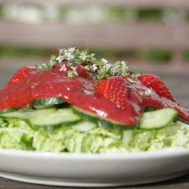 Ein Teller Blattsalat, Gurken, einer roten Soße, garniert mit halbierten Erdbeeren und Kräutern
