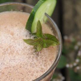Ein Glas mit einem rosa Drink, dekoriert mit einer Gurkenscheibe und Pfefferminzblättern