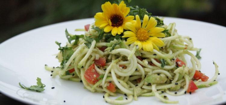 Ein weißer Teller mit Pasta, dekoriert mit gelben Blüten und frischen Kräutern