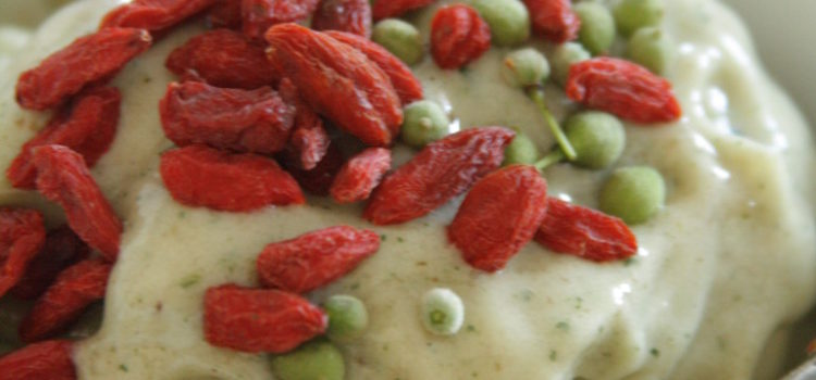 Ein Schüssel mit schmelzender Eiscreme, dekoriert mit Gojibeeren und Lindenfrüchten