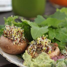 Gefüllte Champignons auf einem Teller mit Wildkräutern und Avocado-Creme