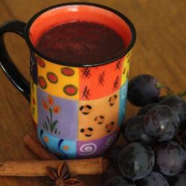 Eine bunte Tasse mit Punsch auf einem Holztisch. Davor liegen blaue Weintrauben, Zimtstangen und Sternanis