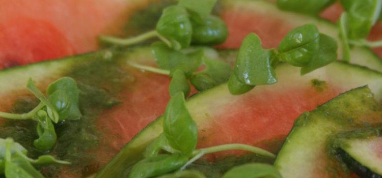 Wassermelonenscheiben garniert mit Pesto und jungen Basilikumblättern