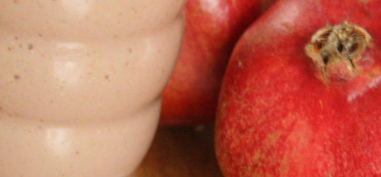 Ein rosa Smoothie in einem Glas, zwei Granatäpfel im Hintergrund