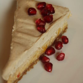 ein Stück Vanillekuchen garniert mit Granatapfel